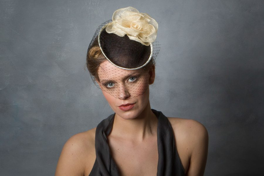 a classic blank and cream cocktail style hat out of sinamay with black birdcage veiling.