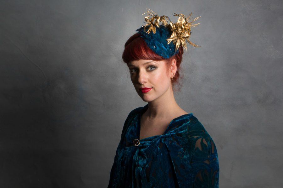 The base is layered deep teal feathers, and is adorned with flowers which are gold and gold-leafed.