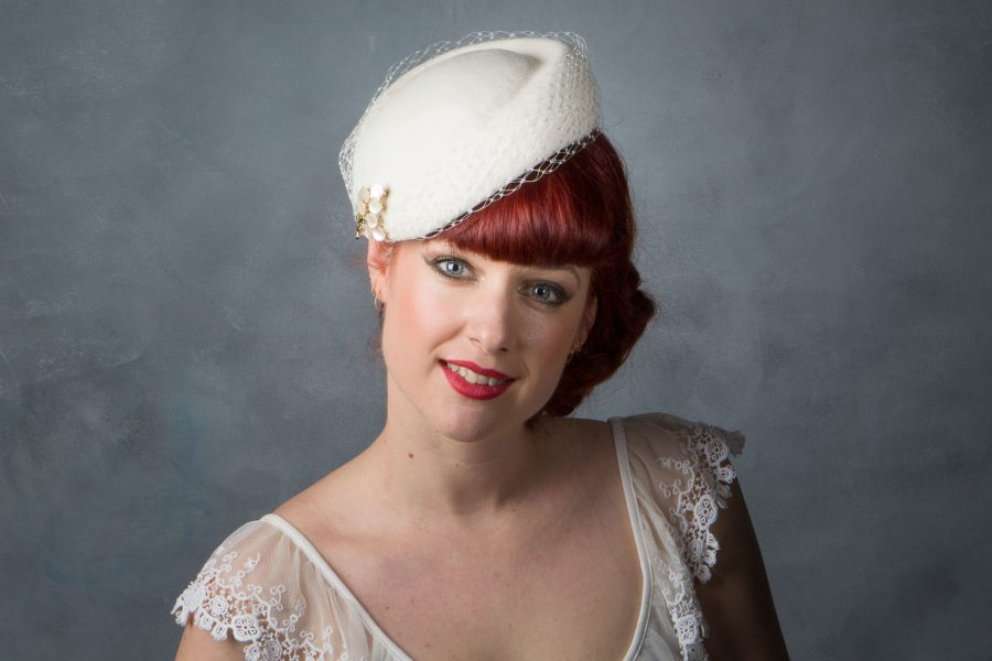 This hat has several ways of being worn and is actually the same as the '1950s Style Bridal Pillbox Hat' – it can simply be worn at different angles to give a totally different look – essentially you're getting three hats in one! As seen in this photo it is more traditional 'Jackie O Kennedy' pillbox look.  Felt with brooch detail with birdcage veil around the edge of the hat. Fixed with millinery elastic.