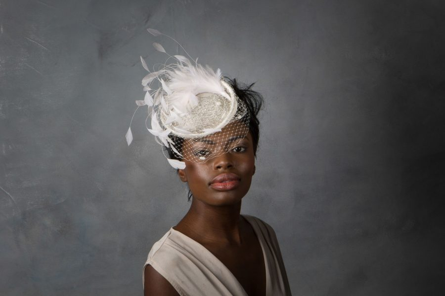 Cocktail hat base with a spray of feathers and dotted birdcage veil. Held with millinery elastic, one size fits all.