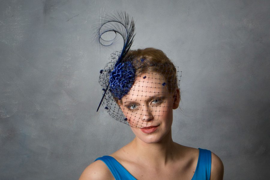 This velvet fascinator is made up of a variety of blues and is ideal for evening events, winter weddings, or less traditional daytime weddings and events. Embedded with Crystal beading and adorned with curled pheasant feather and birdcage veil, this is a small fascinator but with lots of impact and sparkle.